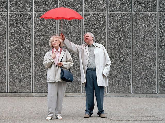 Ein Mann hält einen roten Regenschirm über eine Frau.