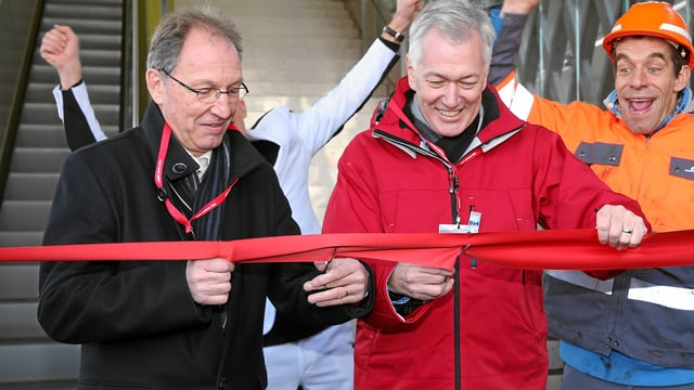 Il directur da la RhB Hans Amacker (dretg) e Lorenza Schmid, president communal d'Arosa, taglian tras la fascha cotschna ed inaugureschan uschia la nova passarella.