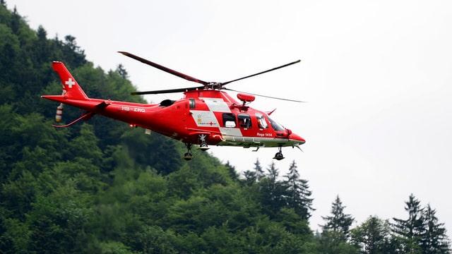 Helikopter der Rettungsflugwacht Rega in der Luft in waldigem Gebiet.