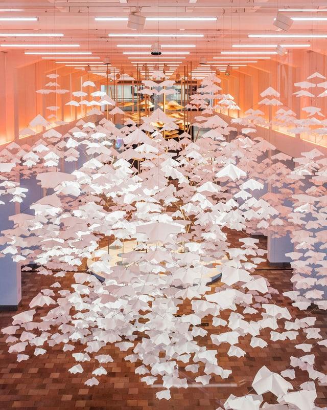 Ein Ausstellungsraum, in dem gefaltete Papiere von der Decke hängen.