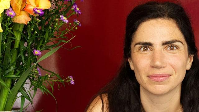 Dana Grigorcea sitzt neben einem Blumenstrauss.