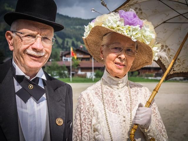 Ein Mann mit Hut und Frack sowie eine Frau im eleganten Kleid mit Strohhut und Sonnenschirm.