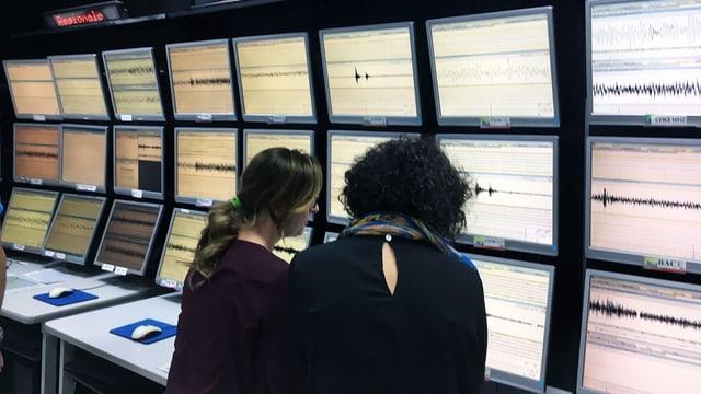 Zwei Frauen stehen vor vielen Monitoren.