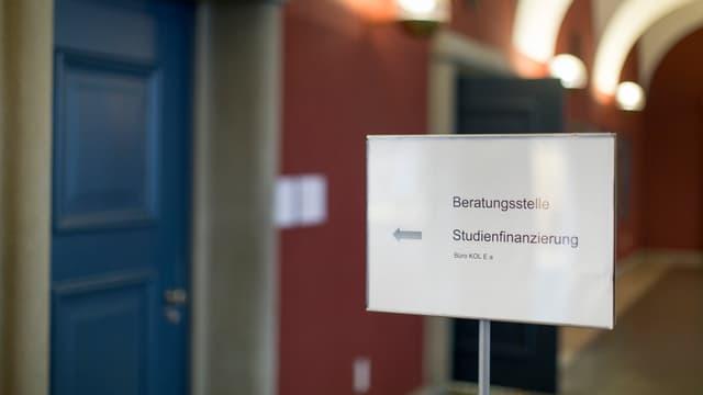 """im Gang der Universität Zürich steht ein Schild mit der Aufschrift """"Beratungsstelle Studienfinanzierung"""""""