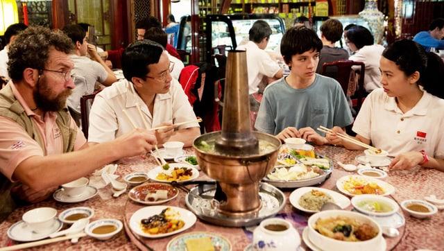 Vier Personen sitzen in einem Restaurant um einen runden Tisch und essen aus kleinen Schälchen.