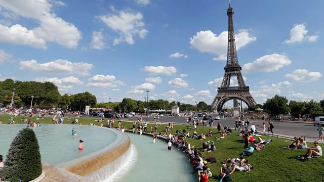 Menschen sitzen an einem Wasserbecken nahe dem Eiffelturm.