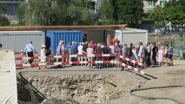 Eine Gruppe Besucher steht vor einem Baucontainer.