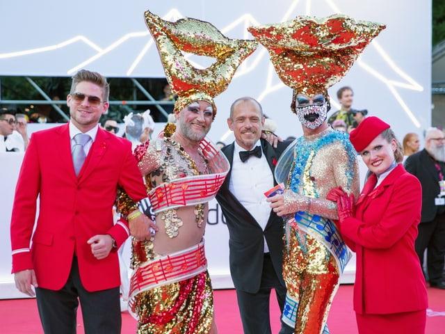 Fünf Menschen auf dem roten Teppich, zwei davon in schillernden Kostümen