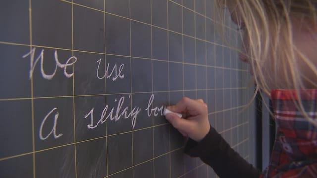 Ein Mädchen schreibt einen Satz an die Tafel