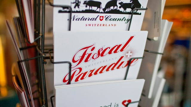 """Kunstpostkarte an der Art Basel 2009 mit der Aufschrift """"Fiscal Paradise"""", gemeint ist die Schweiz."""