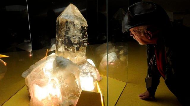 Ein Mann schaut einen Riesenkristall in einer Vitrine an.