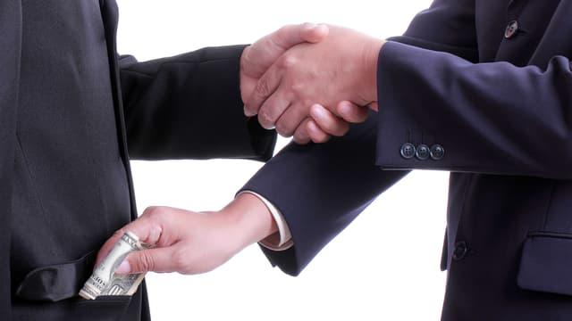 Zwei Männer im Anzug geben sich die Hand. Einer der beiden Männer schiebt dem anderen Geld in die Tasche.