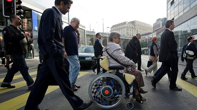 Eine Frau im Rollstuhl überquert die Strasse