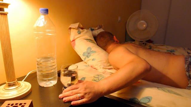 Mann liegt mit nacktem Oberkörper im Bett neben einem Ventilator