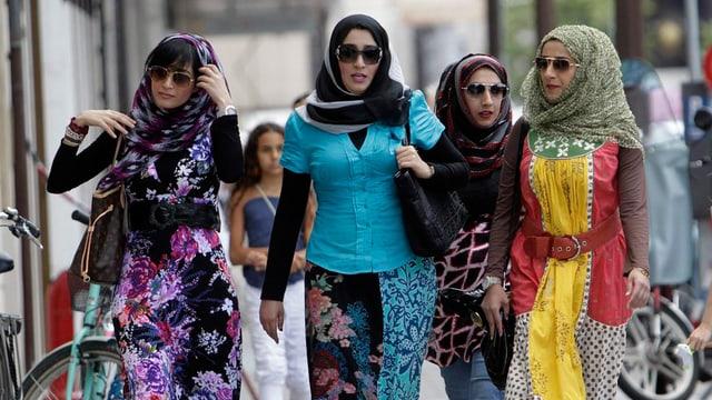 Eine Gruppe Mädchen mit Kopftuch läuft nebeneinander durch eine Einkausstrasse.