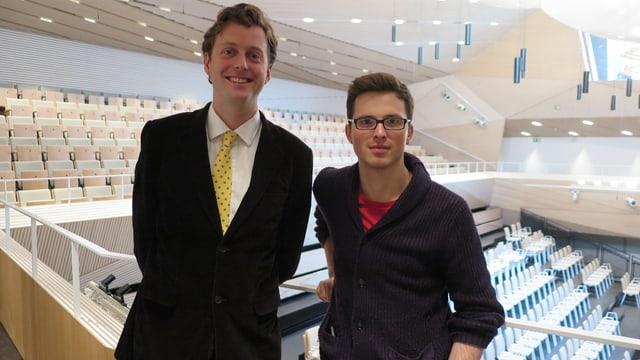 Zwei junge Männer stehen in der hellen neuen Konzerthalle.