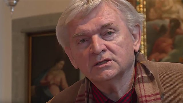 Ein Mann mit grauen Haaren, brauner Jacke und braun-rot-weissem Schal.