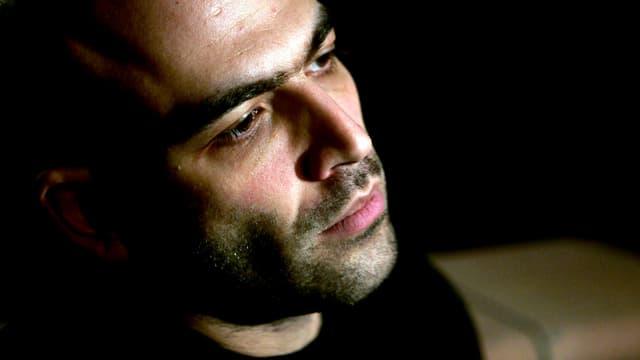 Porträtfoto von Robert Saviano, der im Halbdunkeln steht.