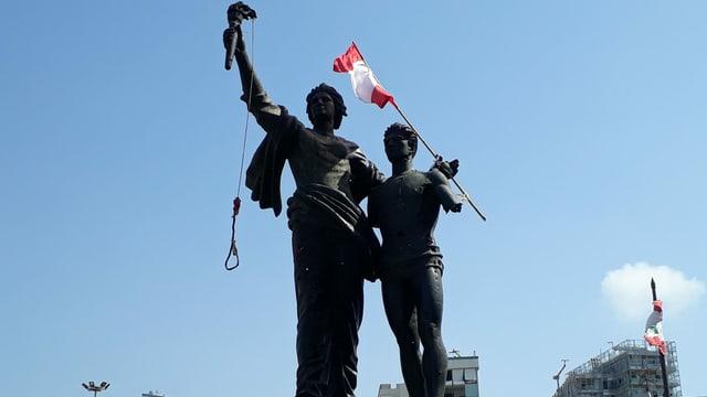 Statue mit 2 Figuren: eine hält Galgen, die andere Libanons Flagge