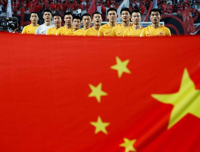 Chinesische Fussballspieler singen die Hymne, davor eine grosse chinesische Flagge.