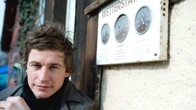 Autor Arno Camenisch an Wetterstation gelehnt