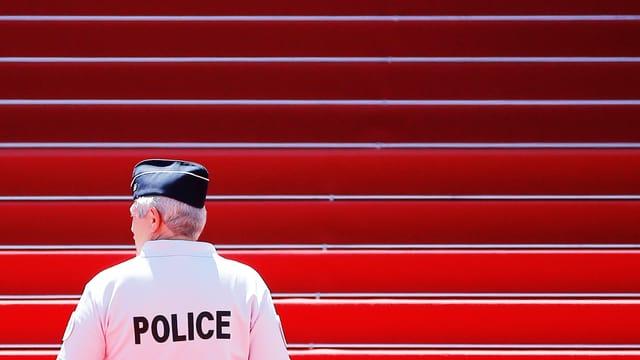 Polizist steht vor Treppe mit rotem Teppich.