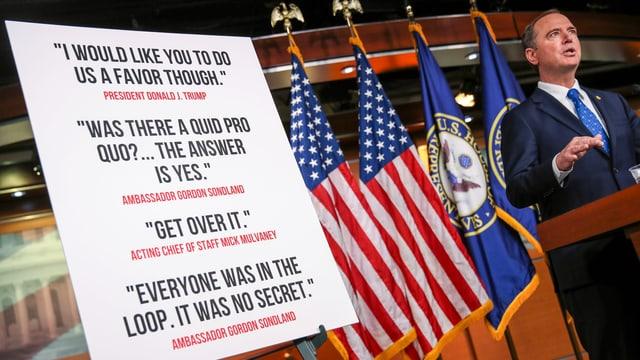 Schiff vor US-Flaggen und einer Tafel mit Headlines.