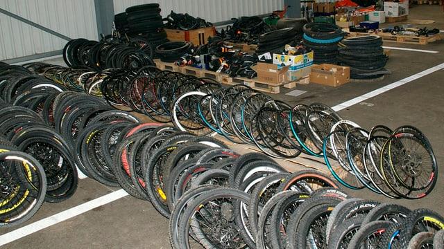 Räder, Pneus und Felgen von Fahrrädern, gestapelt in einer Halle bei der Kantonspolizei St. Gallen.