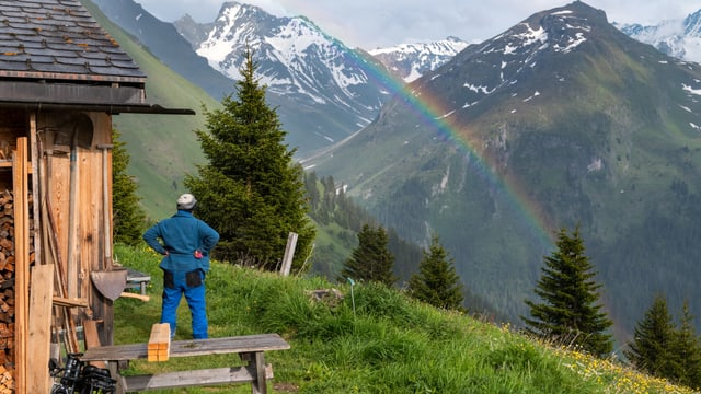 Eine Frau steht vor einer Alphütte und betrachtet einen Regenbogen.