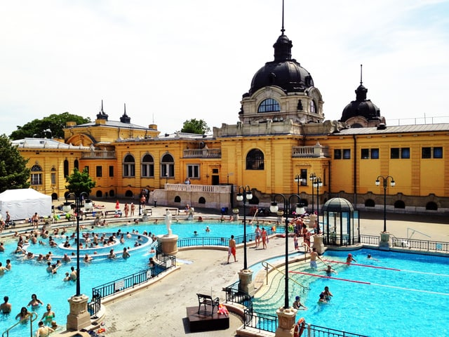 Die Aussenansicht eines neobarocken Bades mit hellblauen Swimmingpools.
