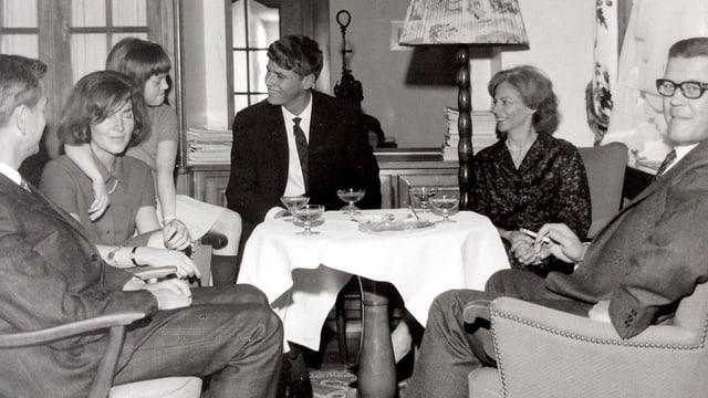 Eine Familie sitzt um ein Sofatischchen, auf dem Champagner-Gläser stehen.
