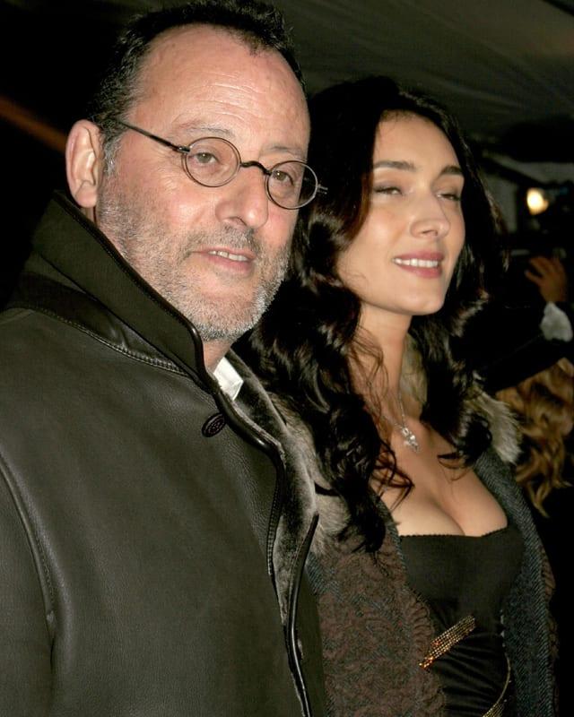 Jean Reno mit seiner Ehefrau lächeln an der Kamera vorbei.
