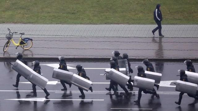 Polizeikräfte gegen in Minsk geben Demonstrierende vor.