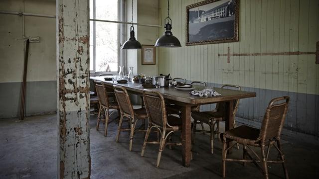 Mittagstisch Fabrik: Ein Tisch mit mehreren Stühlen in einem alten hohen Raum.