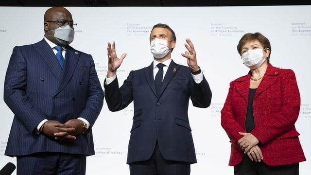 Die drei Personen stehen nebeneinander, Macron in der Mitte gestikuliert.