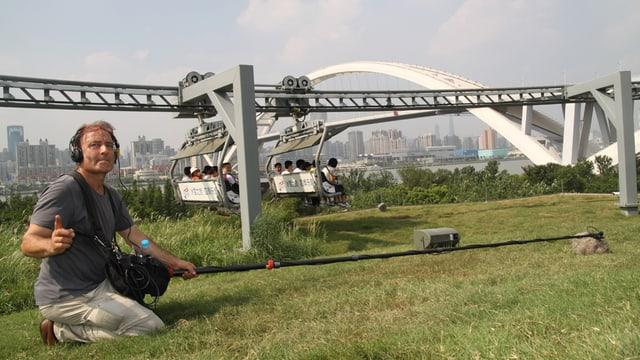 Ein Mann mit einem Stangenmikrophon vor einer Sesselbahn in Shanghai.