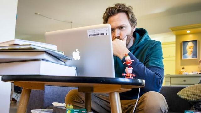 Ein Mann sitzt zu Hause vor einem Laptop.