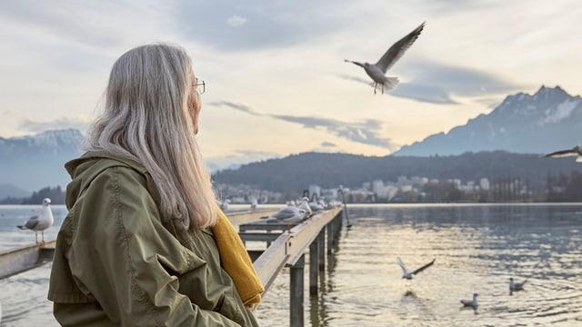 Eine Frau mit langen, grauen Haaren steht am Ufer eines Sees und schaut in die Ferne.