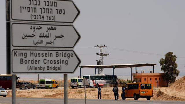 Im Hintergrund der Check-Point an der Allenby-Brücke, im Vordergrund drei Wegweiser in Hebräisch, Arabisch und Englisch.