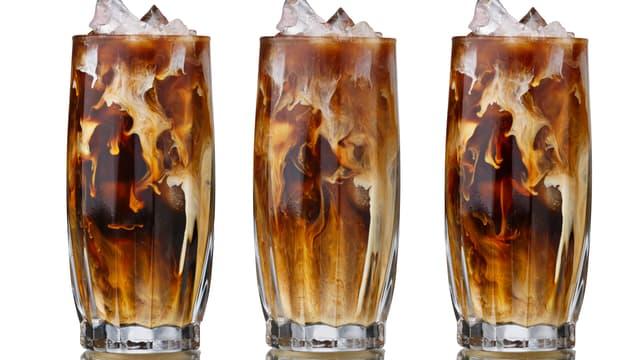 Drei nebeneinander stehede Gläser mit Kaffee und Eiswürfel.