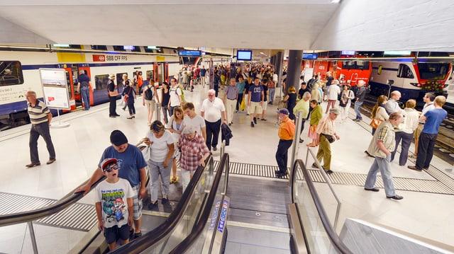Pendler und Pendlerinnen auf dem Perron und auf der Rolltreppe im neuen Bahnhof Löwenstrasse.