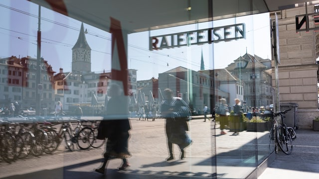 Purtret dal logo da la Raiffeisen spieglà en ina fanestra.