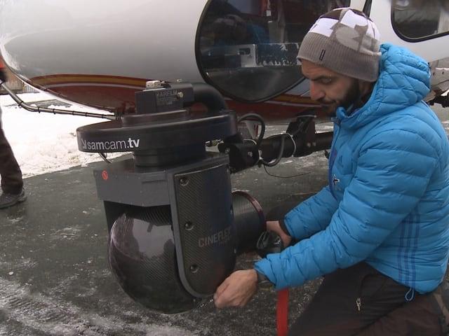 Ein Kameramann montiert eine Cineflex-Kamera an einen Helikopter.