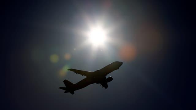 Symbolbild: Flugzeug im Gegenlicht der Sonne am Himmel.