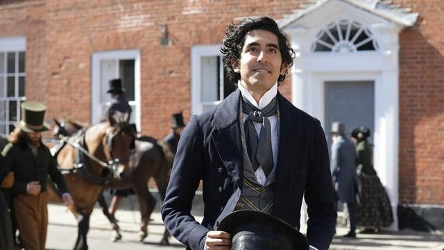 Ein junger Mann, im Hintergrund eine Pferdekutsche.