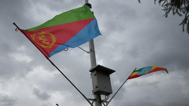 Zwei Flaggen auf einem Mast.