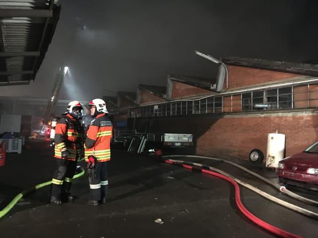 Zwei Feuerwehrmänner vor einer Fabrikhalle.