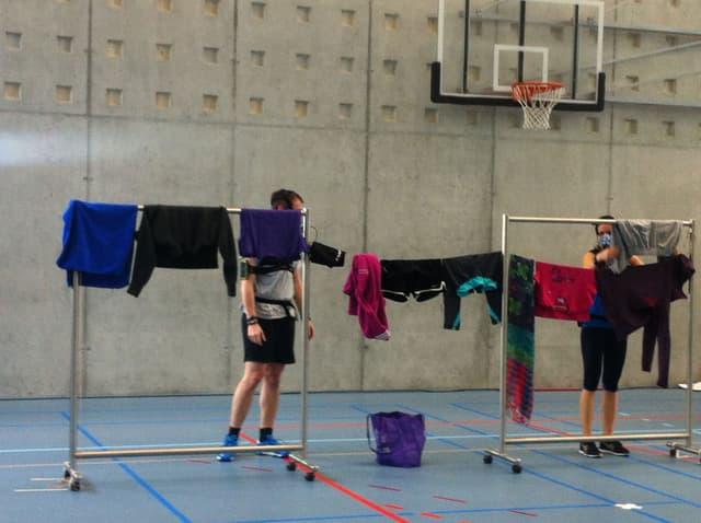 Die Probanden tragen ihre Messgeräte und hängen in einer Turnhalle Wäsche auf.