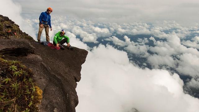 Zwei Bergsteiger auf der Spitze, unter ihnen das Wolkenmeer.