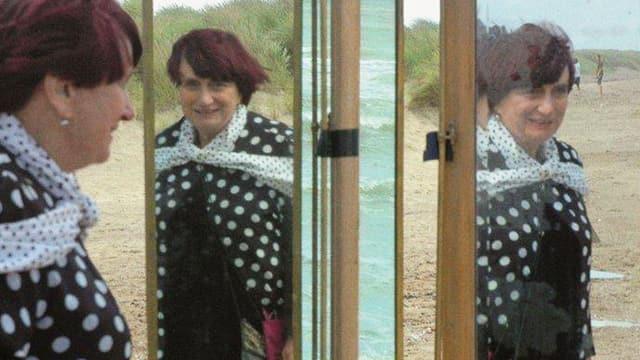 Varda spiegelt sich in mehreren Spiegeln, die an einem Strand stehen